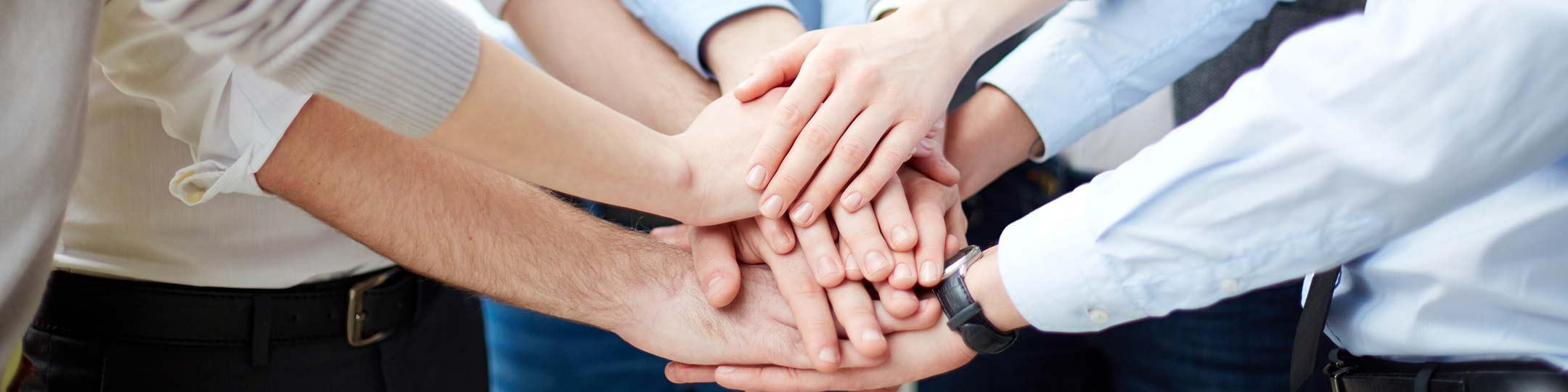Hands clasped together in the centre of a group of people.