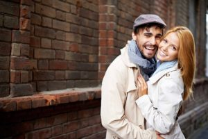 A smiling couple embracing next to a brick building.