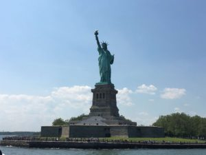Crowds gathered around the statue of liberty on a sunny day.