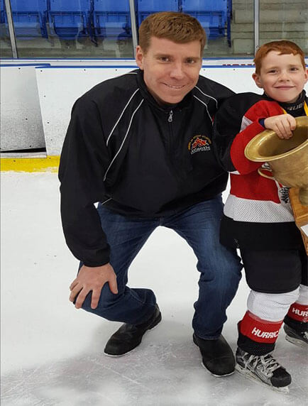 Dr Curtis Gregoire coaching a team of young hockey players